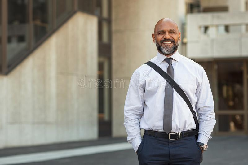 Happy mature businessman standing on street royalty free stock photography