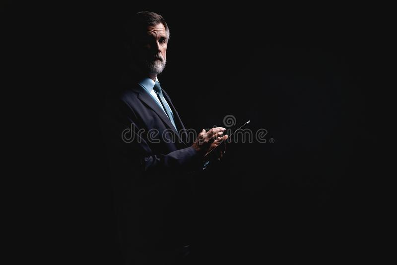 Happy mature businessman working with modern tablet isolated on black background. stock images