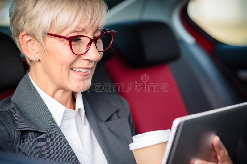 Happy mature businesswoman working on a tablet while commuting to meetin stock photo