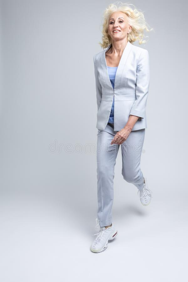 Happy Mature Caucasian Blond Woman in Fashionable Suit Jumping and Moving Against White Background in Studio royalty free stock photos