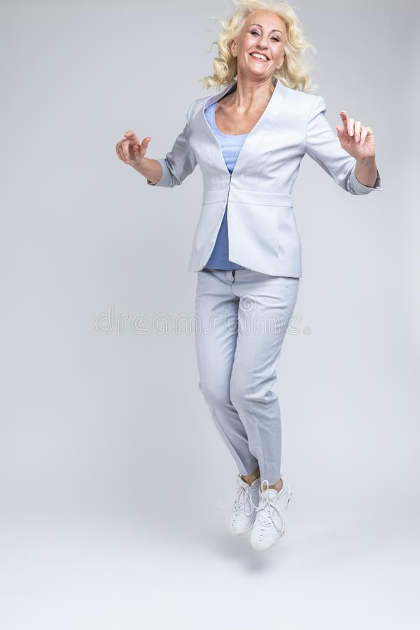 Happy Mature Caucasian Blond Woman in Fashionable Suit Jumping and Moving Against White Background in Studio royalty free stock image