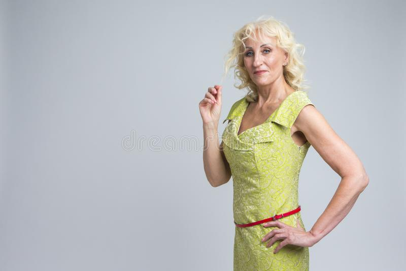 Happy Mature Caucasian Blond Woman Posing in Green Dress Indoors stock image