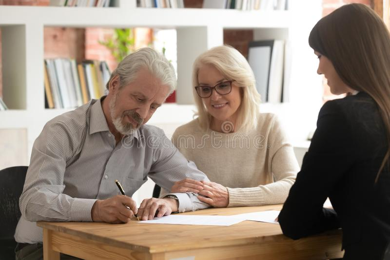 Happy mature clients sign contract closing deal with banker. Happy mature husband and wife sign contract closing deal with female bank specialist taking loan stock photography