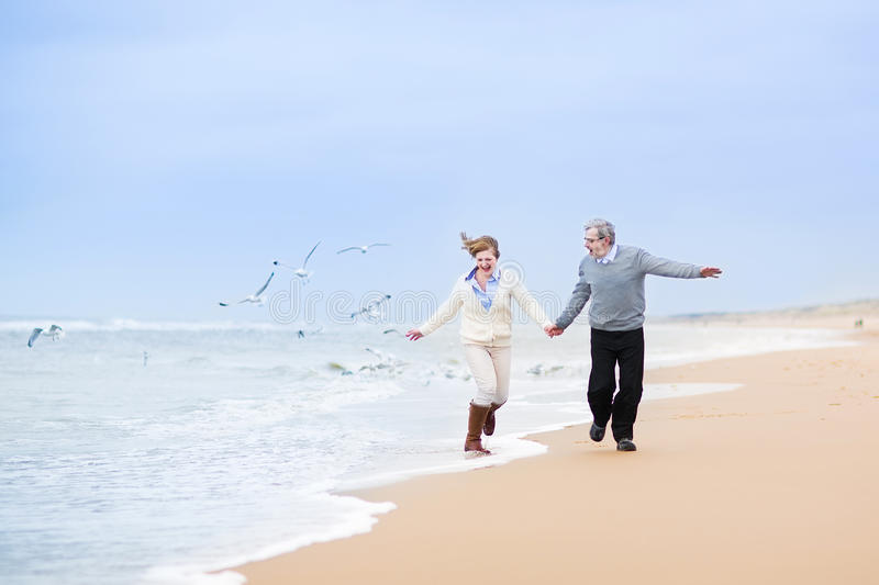 Happy mature couple at beautiful winter beach royalty free stock image