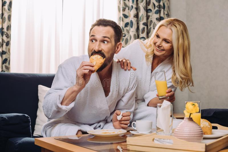 happy mature couple drinking juice and eating pastry during breakfast in hotel stock photo