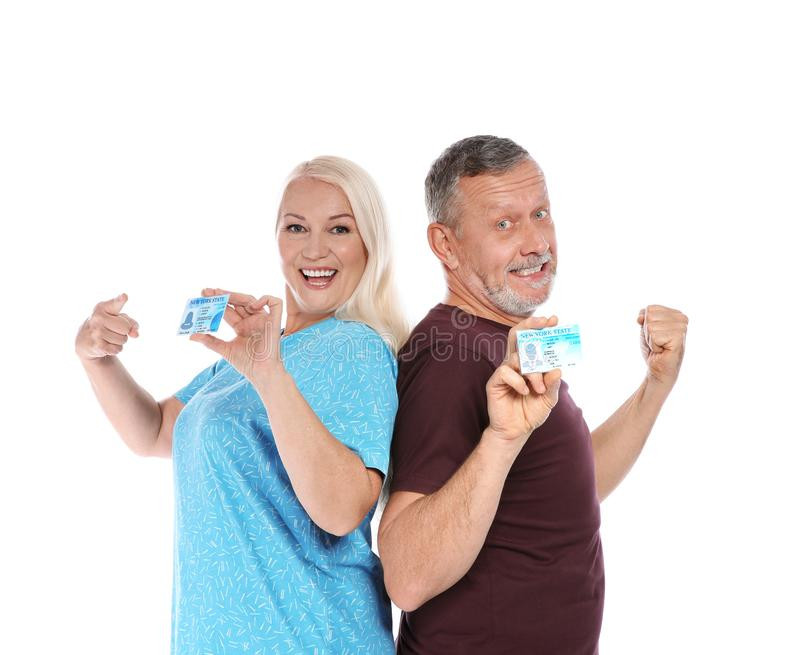 Happy mature couple with driving licenses. On white background stock image