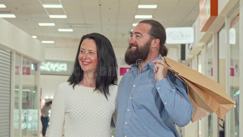 Happy mature couple enjoying seasonal sale at local shopping mall stock photo