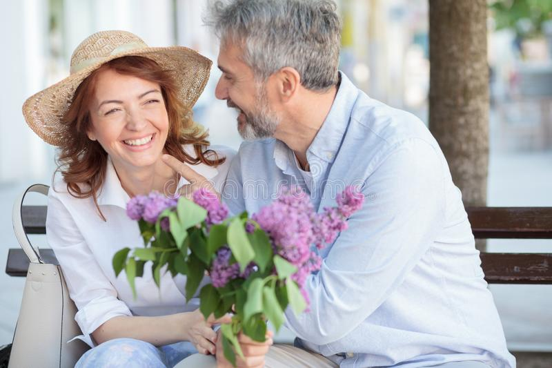 Happy mature couple enjoying their time together, sitting on a bench on town square. Husband giving bouquet of lilac to his wife stock photo