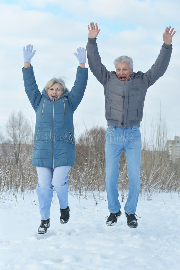 Happy mature couple jumping stock photography