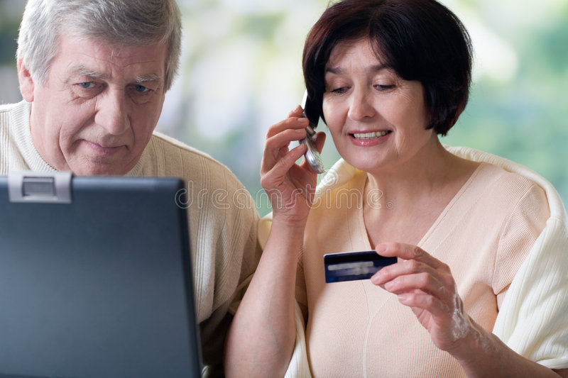 Happy mature couple on laptop, shopping in internet shop stock images