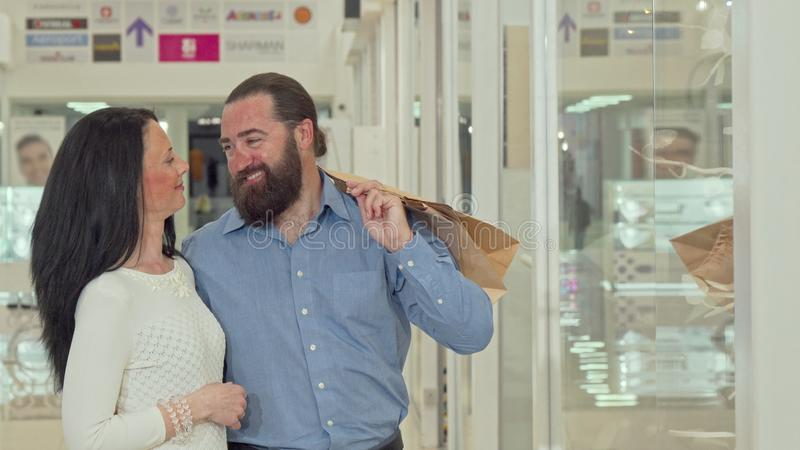 Happy mature couple looking at clothing store showcase at the shopping mall royalty free stock images