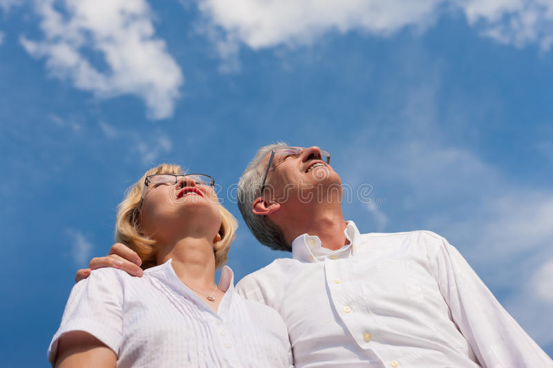 Happy mature couple looking to the blue sky. Happy mature couple - senior people (man and woman) already retired - looking to the blue sky in summer stock image