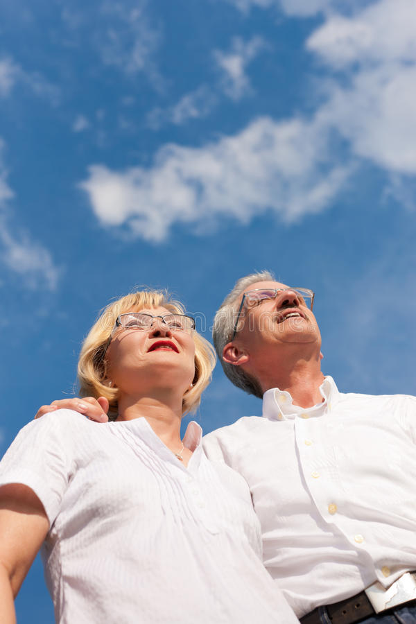 Happy mature couple looking to the blue sky. Happy mature couple - senior people (man and woman) already retired - looking to the blue sky in summer royalty free stock photo