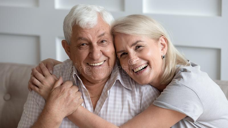 Happy mature couple in love seated on couch embracing. Horizontal banner happy old couple in love seated on couch embracing, laughing grey haired husband and stock photos
