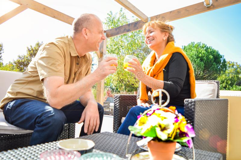 Happy mature couple making a toast staring at each other eyes lovingly and smiling royalty free stock images