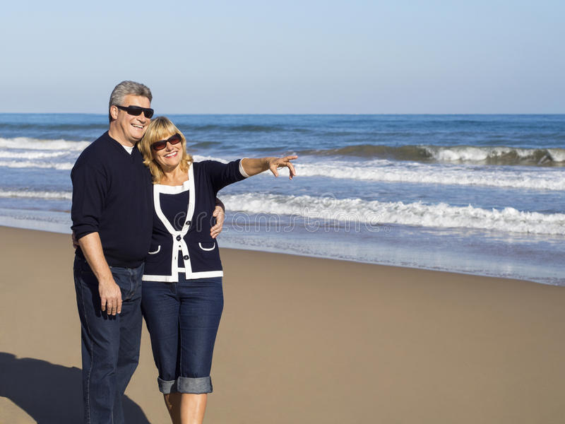 Happy mature couple points to on a sunny day at the beach royalty free stock images