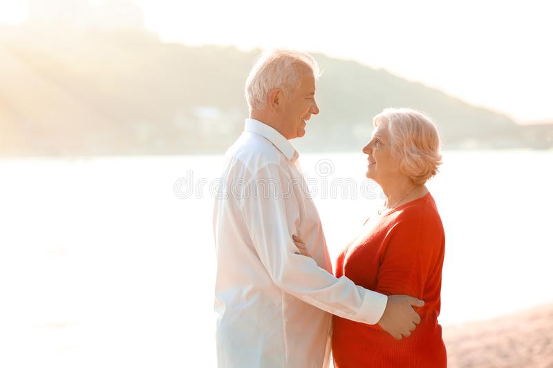 Happy mature couple on riverside stock images