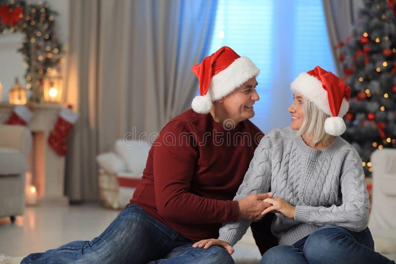 Happy mature couple in Santa hats at home. Christmas. Celebration royalty free stock photos
