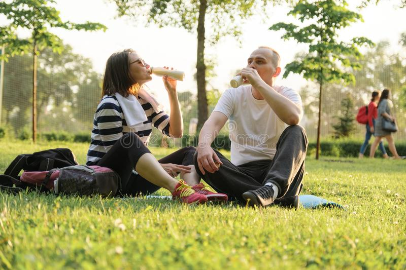 Happy mature couple sitting in the park on fitness mat, resting drinking yogurt after sports exercises royalty free stock photography