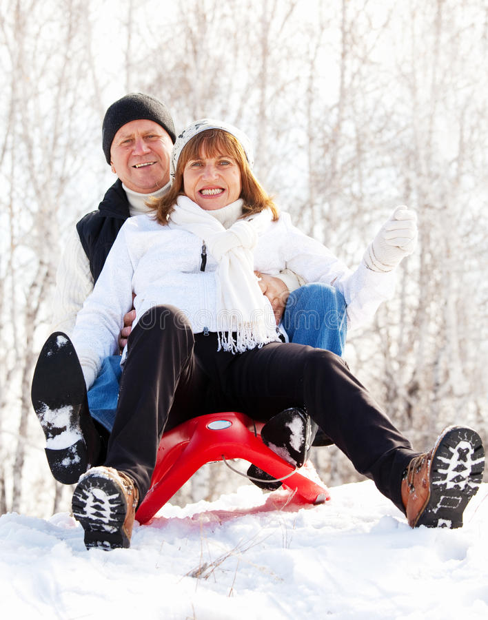 Happy mature couple sledding. Mature couple sledding. Seniors couple on sled in winter park royalty free stock photography
