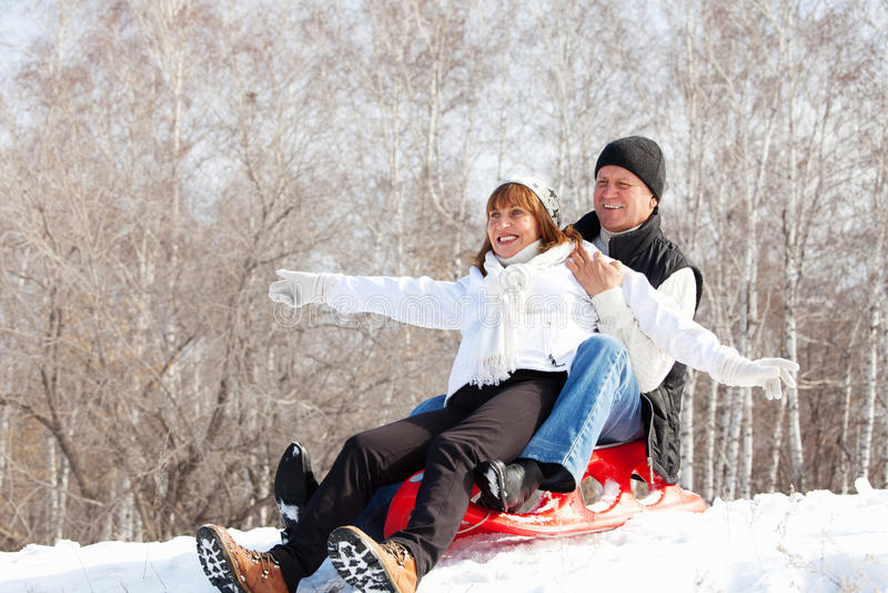 Happy mature couple sledding. Mature couple sledding. Seniors couple on sled in winter park royalty free stock images