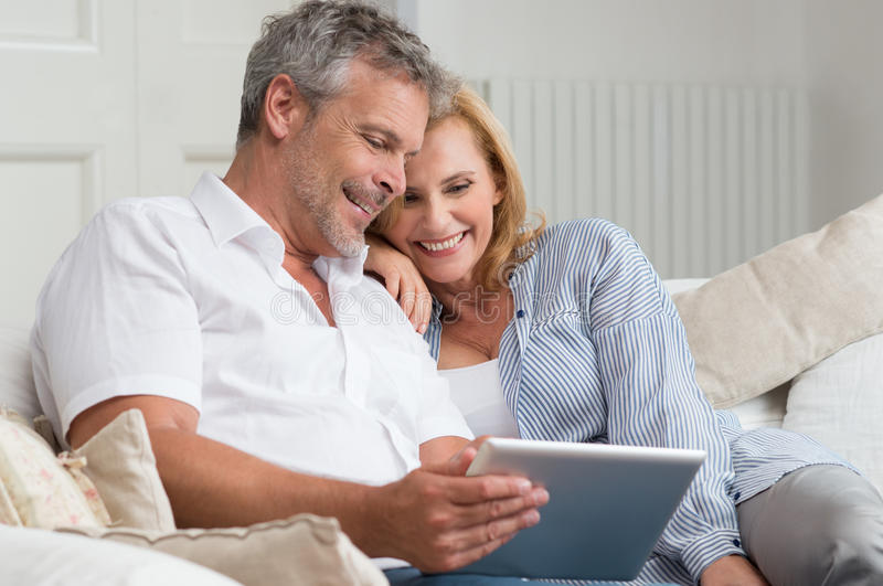 Happy Mature Couple With Tablet. Happy Mature Couple Sitting On Sofa With Digital Tablet