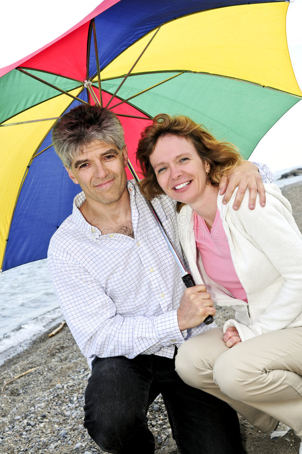 Download Happy Mature Couple With Umbrella Stock Image - Image of multicolored, middle: 5852845