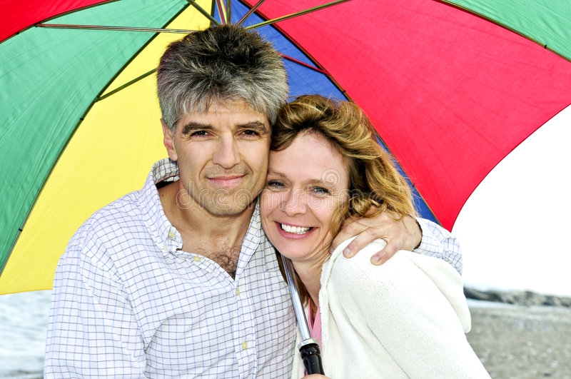 Download Happy Mature Couple With Umbrella Stock Photo - Image of beach, happiness: 5852878