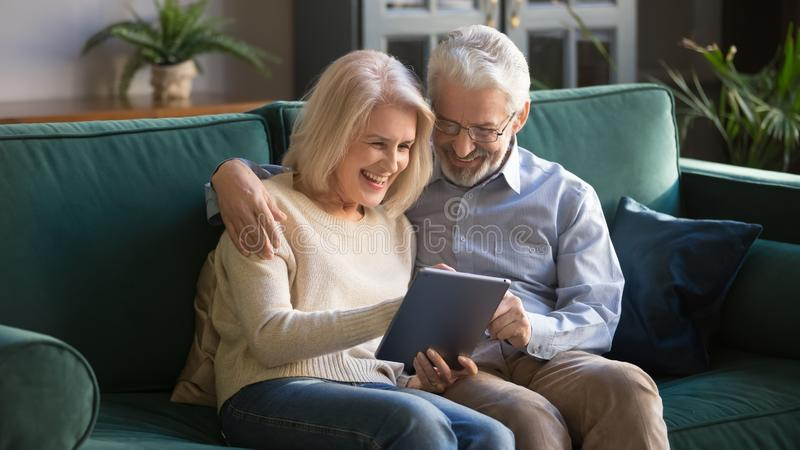 Happy mature family, wife and husband using tablet at home together stock image