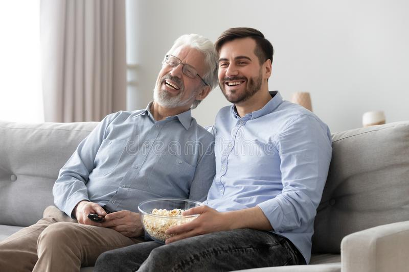 Happy mature father and son watching tv show together stock photography