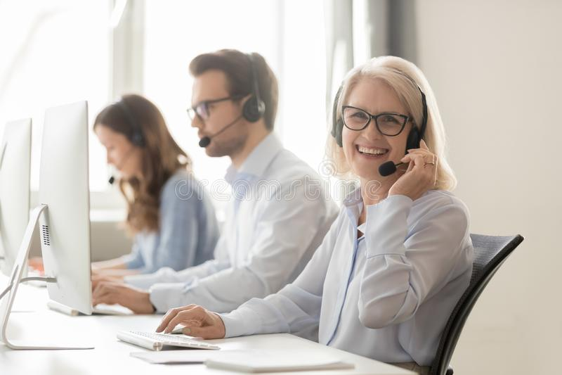 Happy mature female call center agent looking at camera smiling. Happy old mature female call center agent telemarketer looking at camera at work, smiling aged stock image
