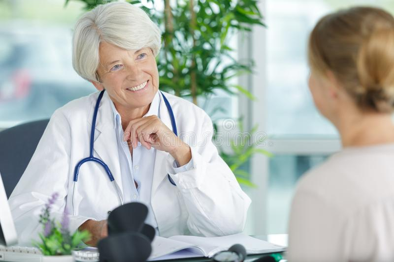 Happy mature female doctor talking to female patient stock photography
