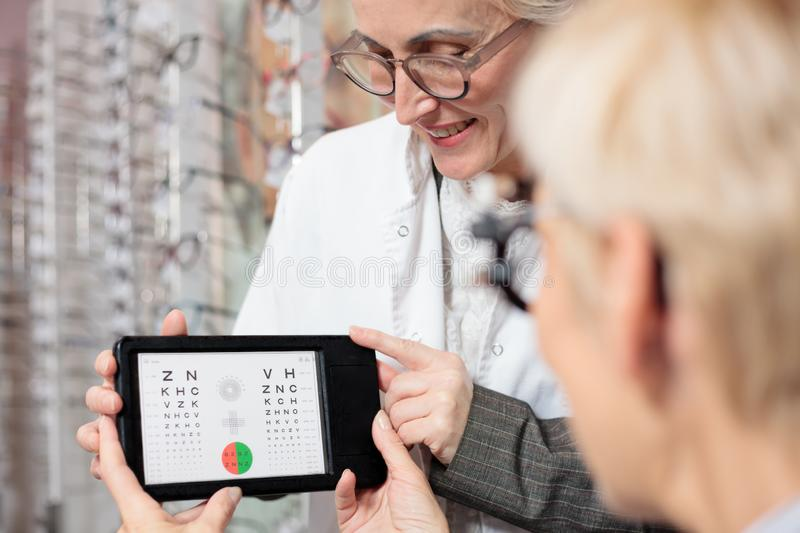 Smiling mature female ophthalmologist testing patient`s vision for myopia with a test chart. Happy mature female ophthalmologist testing patient`s vision for stock image