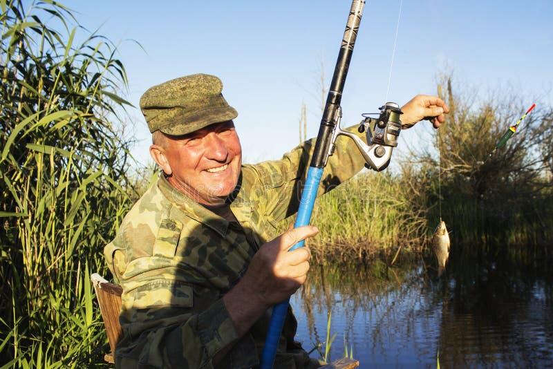 Happy mature fisherman with fresh caught crucian stock image