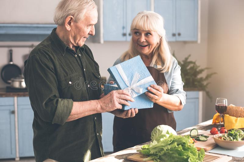 Happy mature lady receiving present from husband. Excited senior women is opening gift box and laughing. Man is greeting her with holiday in kitchen stock photography