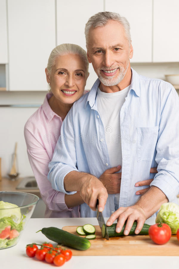 Happy mature loving couple family cooking salad stock photo