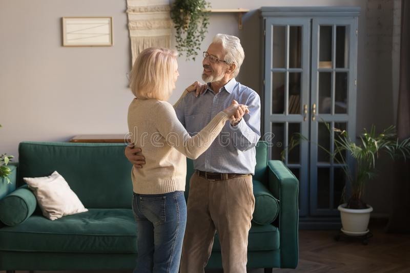 Happy mature loving couple, wife and husband dancing at home stock photos