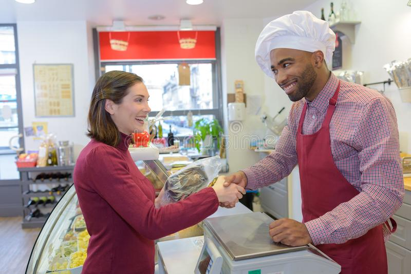 Happy mature male butcher selling fresh meat to female customer royalty free stock photography