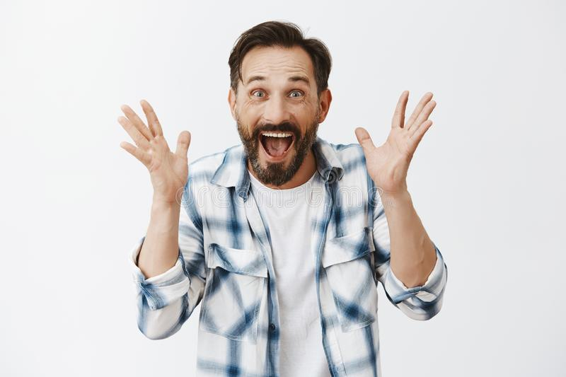 Happy mature male cannot control emotions, feeling happiness and joy, screaming from amazement and excitement, shaking stock image