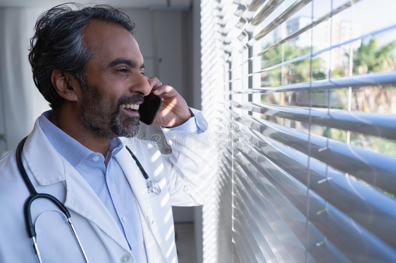 Happy mature male doctor talking on mobile phone in hospital. Side view of happy mature mixed race male doctor talking on mobile phone in hospital royalty free stock images