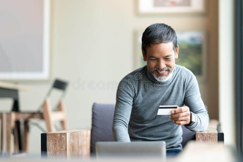 Happy mature man holding credit card paying online by using laptop for payment. Asian senior male smiling shopping online with omni channel concept at coffee stock images