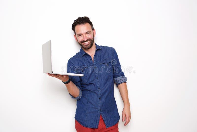 Happy mature man holding laptop. Portrait of happy mature man holding laptop over white background royalty free stock photo
