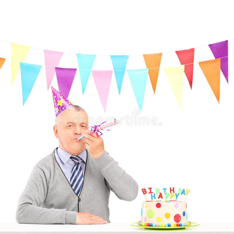 A happy mature man with party hat blowing and a birthday cake. Isolated on white background stock image