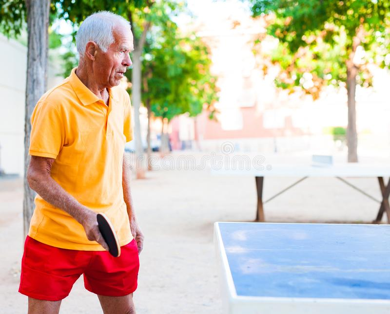 Mature man playing table tennis. Happy mature man playing table tennis royalty free stock photography