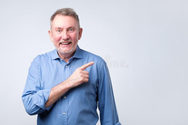 Happy mature man in shirt looking at camera and pointing away royalty free stock image