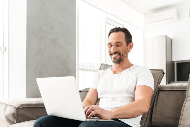 Happy mature man sitting on a sofa stock photos