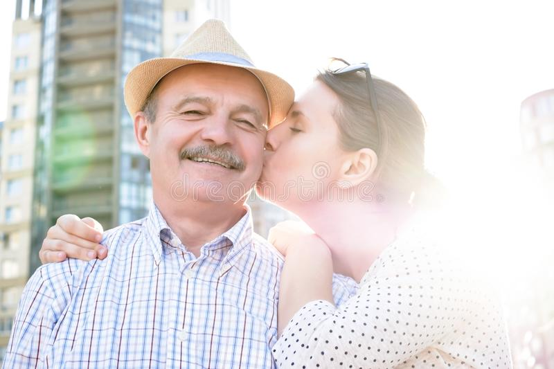 Happy mature man smiling with young woman. Portrait of a happy mature men smiling with young woman. Hispanic father in summer hat and daughter walking outdoor stock photos