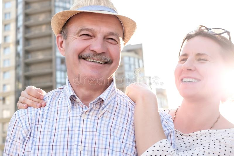 Happy mature man smiling with young woman. Portrait of a happy mature men smiling with young woman. Hispanic father in summer hat and daughter walking outdoor stock photography