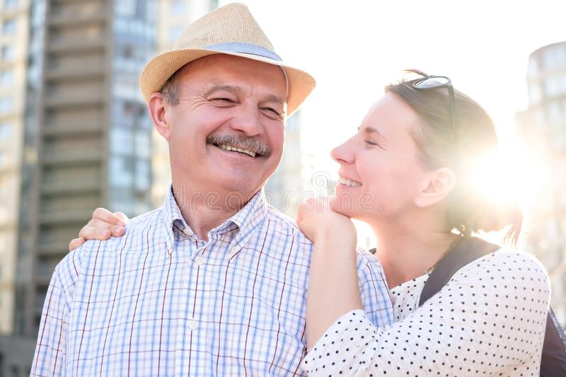 Happy mature man smiling with young woman. Portrait of a happy mature men smiling with young woman. Hispanic father in summer hat and daughter walking outdoor stock photo