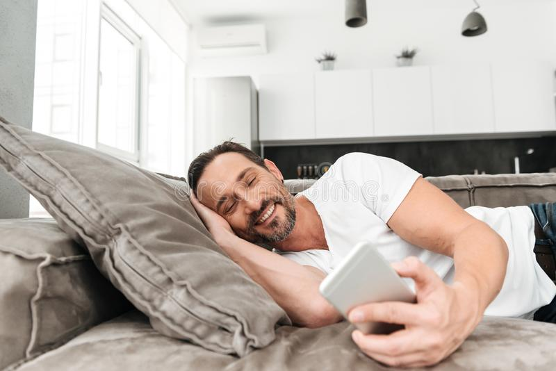 Happy mature man using mobile phone royalty free stock photography